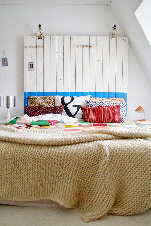 Dormitorio, cabecero de tablillas de madera y mucho color en los textiles de la cama
