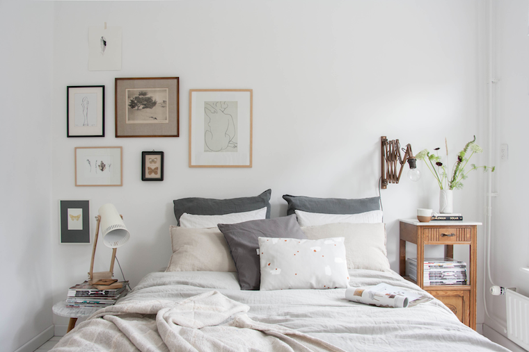 Decoracion-dormitorio-composicion-de-cuadros-en-tonalidades-grises-y-marrones-mesita-de-noche-vintage